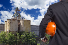 Engineer holding helmet working at high building construction site Royalty Free Stock Photos