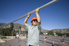 Engineer Holding Metallic Pole On Rooftop Against Sky Stock Photo