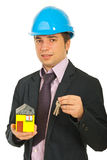 Engineer holding miniature home and keys Royalty Free Stock Image
