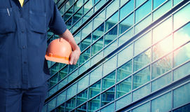 Engineer holding orange helmet for workers security Royalty Free Stock Photo