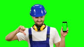 Engineer is holding a phone in his hand and showing his finger down. Green screen. Mock up. Engineer in the helmet is holding his phone in his hands and showing stock footage