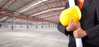 Engineer holding plan and helmet at warehouse Royalty Free Stock Photo