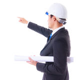 Engineer holding plan and pointing to construction site Royalty Free Stock Image