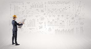 Engineer holding a plan and standing with graphs, charts and reports on the background royalty free stock photo