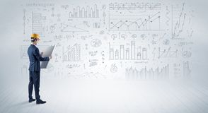 Engineer holding a plan and standing with graphs, charts and reports on the background stock photography