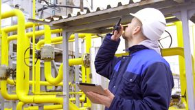 Engineer holding a tablet, talking on walkie-talkie in modern industrial factory