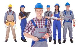Engineer holding tool with team against white background Stock Photos