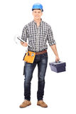 Engineer holding a toolbox and a clipboard. Full length portrait of an engineer holding a toolbox and a clipboard isolated on white background Royalty Free Stock Image