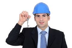 Engineer holding up a key Royalty Free Stock Photo