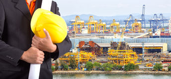 Engineer holding yellow helmet and plan. For workers security on background of harbor on background royalty free stock photos