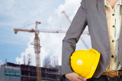 Engineer holding yellow helmet for workers security on backgroun Stock Images