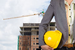 Engineer holding yellow helmet for workers security on backgroun Stock Photography
