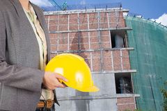 Engineer holding yellow helmet for workers security on backgroun Stock Photos
