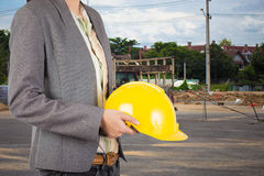 Engineer holding yellow helmet for workers security on backgroun Royalty Free Stock Photo