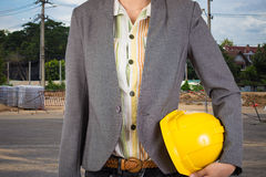 Engineer holding yellow helmet for workers security on backgroun Royalty Free Stock Image