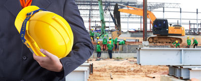 Engineer holding yellow helmet for workers security. On background of new warehouse buildings and group of worker working hard Stock Images