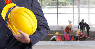 Engineer holding yellow helmet for workers security. On background of new warehouse buildings and worker working hard Royalty Free Stock Images