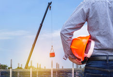 Engineer holding yellow safety helmet in building construction site Royalty Free Stock Image