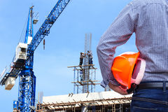 Engineer holding yellow safety helmet in building construction site with crane Stock Photo