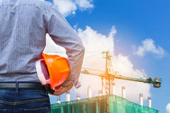 Engineer holding yellow safety helmet in building construction site with crane Royalty Free Stock Photos