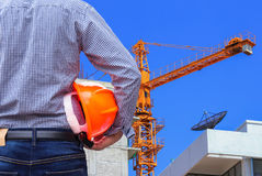 Engineer holding yellow safety helmet in building construction site with yellow crane Royalty Free Stock Image