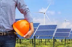 Engineer holding yellow safety helmet front solar photovoltaic and wind turbines power station Royalty Free Stock Photo