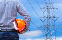 Engineer holding yellow safety helmet with high voltage electric pylon pillars Royalty Free Stock Photos