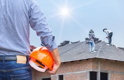 Engineer holding yellow safety helmet at new home building with workers installing concrete tile royalty free stock image