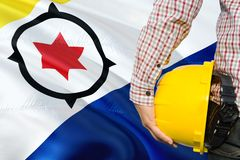 Engineer is holding yellow safety helmet with waving Bonaire flag background. Construction and building concept royalty free stock images