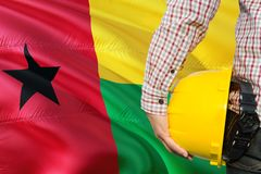 Engineer is holding yellow safety helmet with waving Guinea Bissau flag background. Construction and building concept.  stock photos