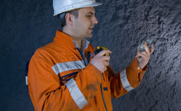 Engineer inspecting mineral. With flashlight stock photo Stock Photography