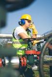 Engineer  inspecting a valve Stock Photo
