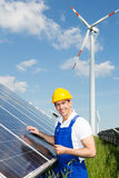 Engineer inspects solar panels at energy park. Engineer inspecting solar panels at energy park in front of wind turbine Royalty Free Stock Photography