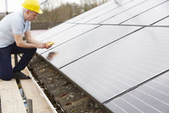 Engineer Installing Solar Panels On Roof Of House. Engineer Installs Solar Panels On Roof Of House Royalty Free Stock Images