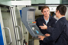 Engineer Instructing Trainee On Use Of Computerized Cutting Mach. Engineer Instructs Trainee On Use Of Computerized Cutting Mach royalty free stock image