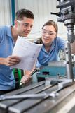 Engineer Instructing Female Apprentice On Use Of Drill. Engineer Instructs Female Apprentice On Use Of Drill royalty free stock photos