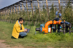 Engineer with irrigation system in orchard Stock Image