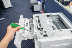 Engineer left hand use green screwdriver repair office printer tray. And other parts Royalty Free Stock Photo