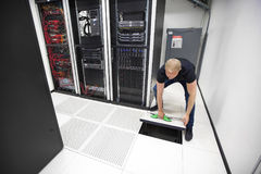 IT Engineer Lifting Floor Tile Using Suction Cups In Datacenter. Full length of male IT engineer lifting floor tile using vacuum suction cups in datacenter Stock Photography