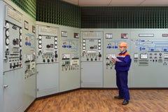 Engineer with log on main control panel Stock Photos