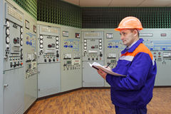 Engineer with log on main control panel Stock Photography