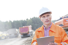 Engineer looking away while holding clipboard against clear sky Royalty Free Stock Photo