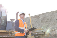 Engineer looking away while holding clipboard at construction site Royalty Free Stock Photography