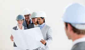 Engineer looking back at his smiling colleagues Stock Photos