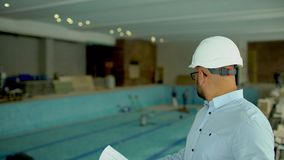 Engineer looking at building plans in construction site. On the background of the pool under construction. 4 k the design of the pool. construction of the pool stock video footage