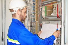 Engineer is looking at electrical drawing diagram in electrical automation cabinet and control of industrial equipment. Royalty Free Stock Photography