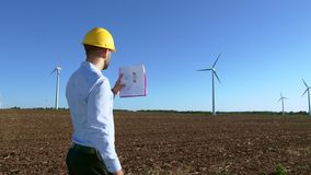 Engineer looks at the windmill drawings on the background of a windmill. stock video footage