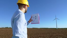 Engineer looks at the windmill drawings on the background of a windmill and makes marks. stock video footage
