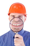 Engineer and magnifying glass. Civil engineer holding a magnifying glass to his mouth and smiling toothy grin royalty free stock images