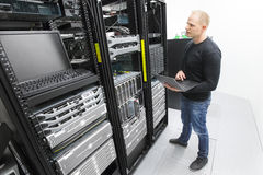 It engineer maintains servers in datacenter Stock Photography